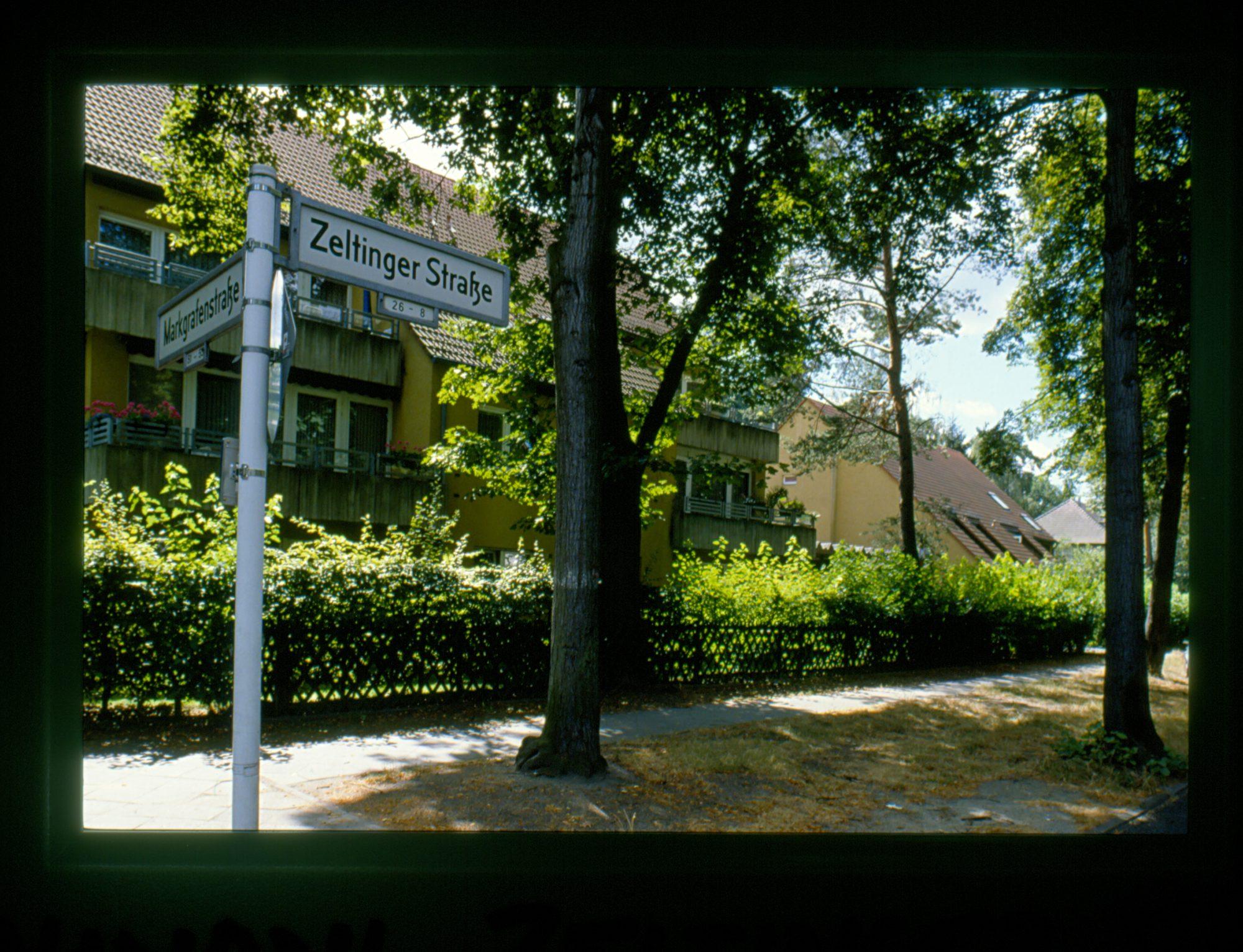 """Zu sehen ist ein eine eher grüne Straße in Berlin mit ein paar Häusern im Hintergrund. Im Bildvordergrund steht das Straßenschild """"Zeltinger Straße""""."""