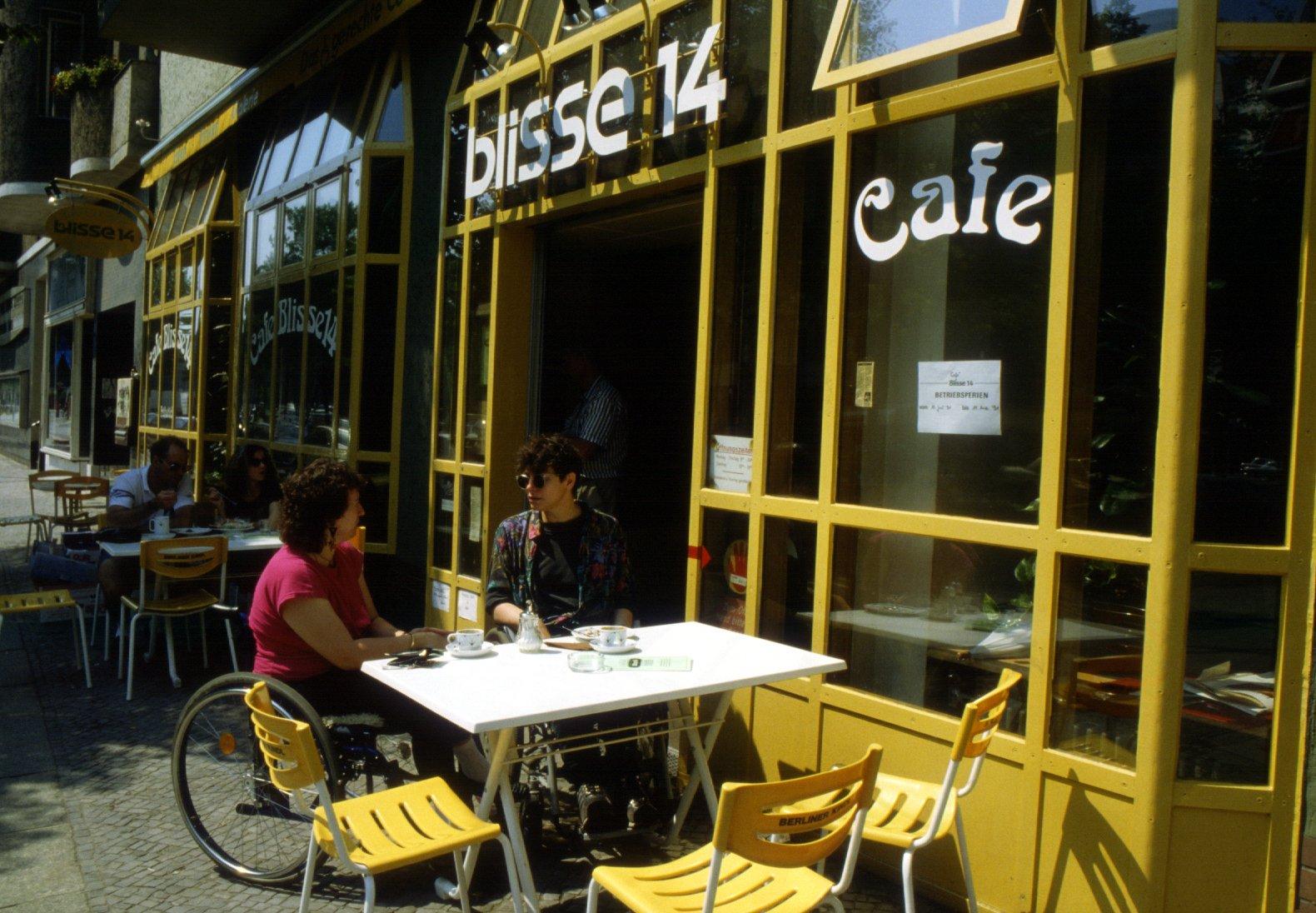"""Außenansicht der """"blisse 14"""". Zwei Menschen im Rollstuhl sitzen außen, die Fassade ist gelb. Die Aufschrift """"blisse 14"""" Cafe."""