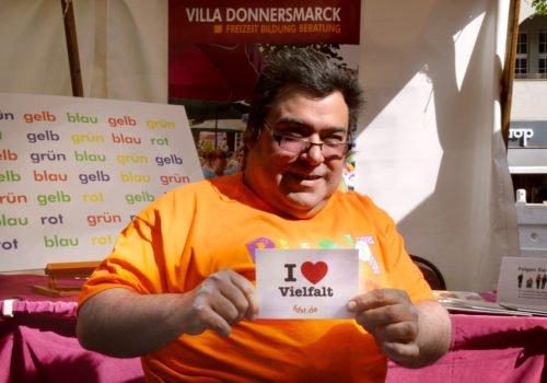 Mann im Rollstuhl bei der Aktion Bunt verbindet im Vorjahr (2018). Er hält eine Postkarte mit der Aufschrift I ❤ Vielfalt nach oben.