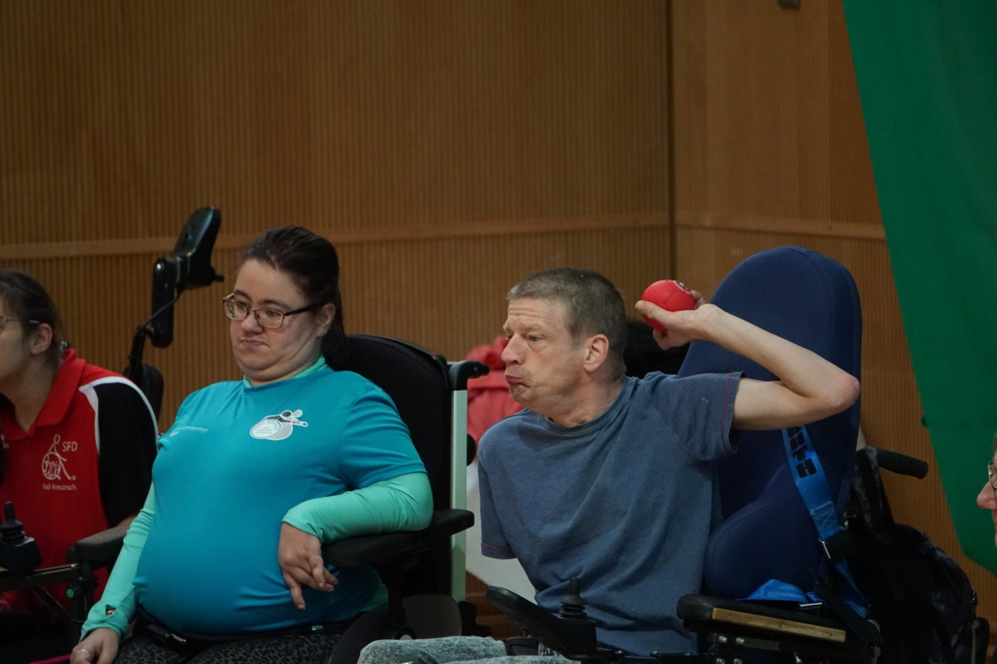 Das Bild zeigt eine Wurfsituation: Ein E-Rollstuhlfahrer ist gerade dabei, einen roten Ball loszulassen. Eine Mitspielerin links neben ihm schaut dabei zu.