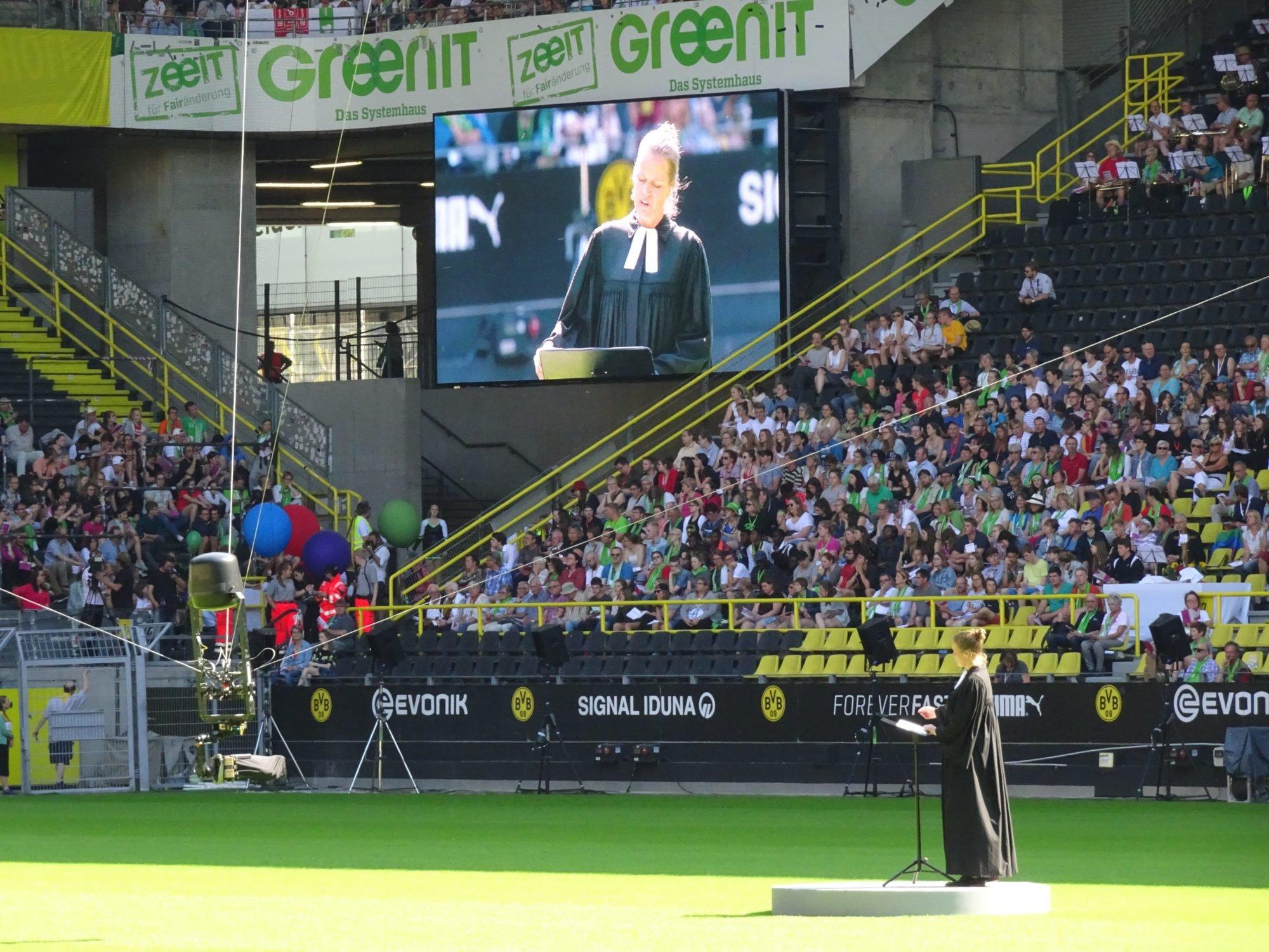 Eine Frau im schwarzen Talar steht auf dem Fußballfeld. Sie hält die Predigt. Im Hintergrund ist Signal Iduna und Evonik zu lesen. Es ist das Stadion von Borussia Dortmund.