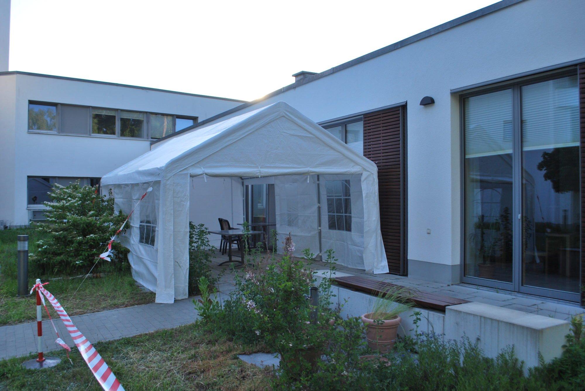Das Bild zeigt einen Teil des P.A.N. Zentrums von außen. Davor ist ein Pavillon aufgebaut, der als Besuchermöglichkeit dient. Ein weißes Zelt, der Weg dorthin ist mit einem Flatterband abgegrenzt.