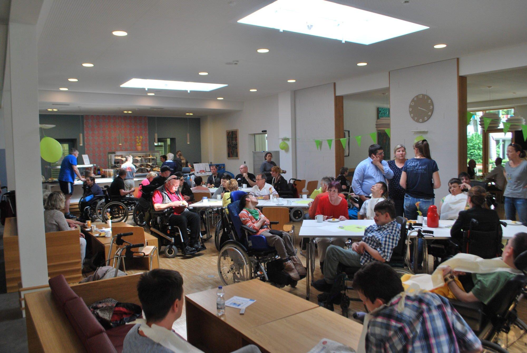 Der Tag der Nachbarn im vollen Gange: das Foyer ist voll mit Menschen. Viele davon im Rollstuhl.