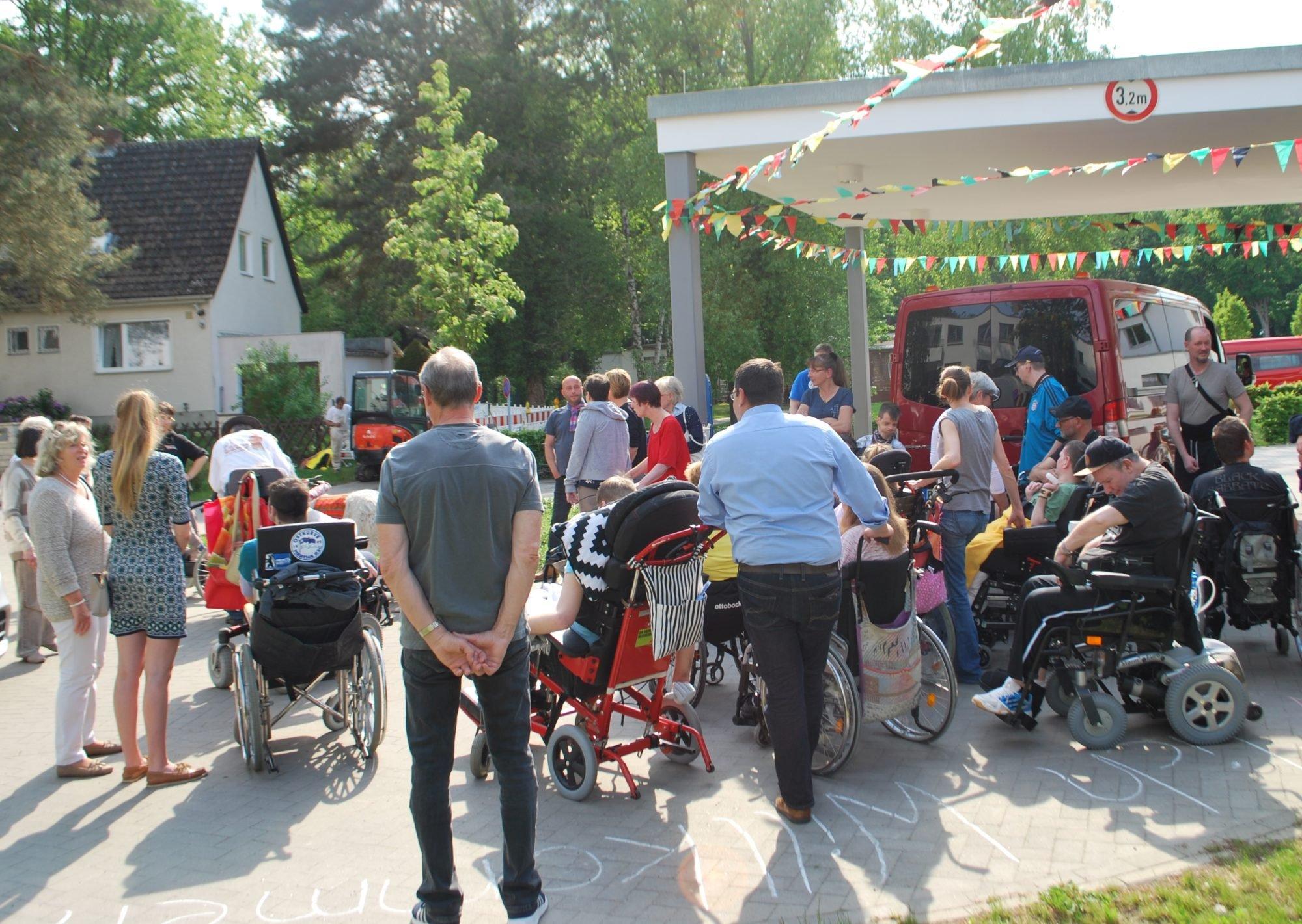 Auch vor dem Gebäude ist viel los: Viele Menschen stehen vor dem Eingangsbereich des P.A.N. Zentrums und unterhalten sich - viele davon im Rollstuhl.