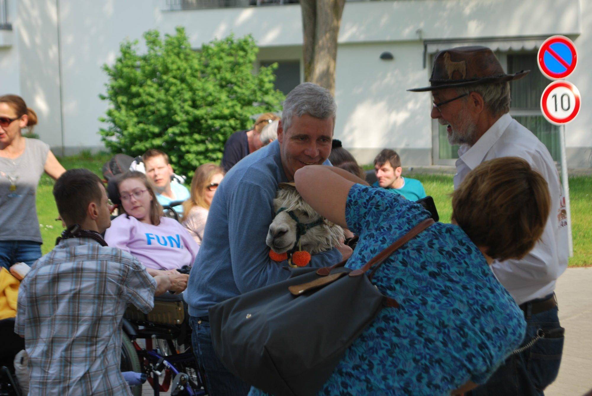 Ein Herr und eine Dame kuscheln das Alpaka. Im Hintergrund sitzen mehrere Menschen beieinander.