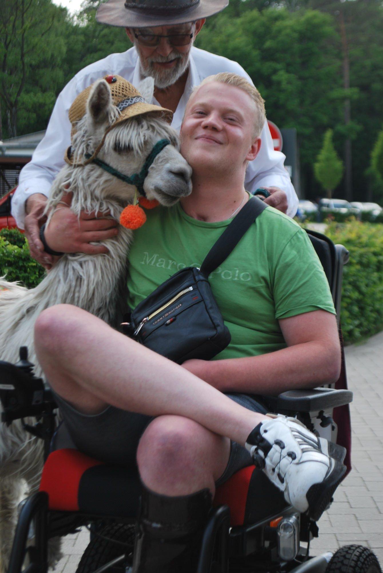 Ein Rehabilitand im Rollstuhl lässt sich mit dem Alpaka fotografieren.