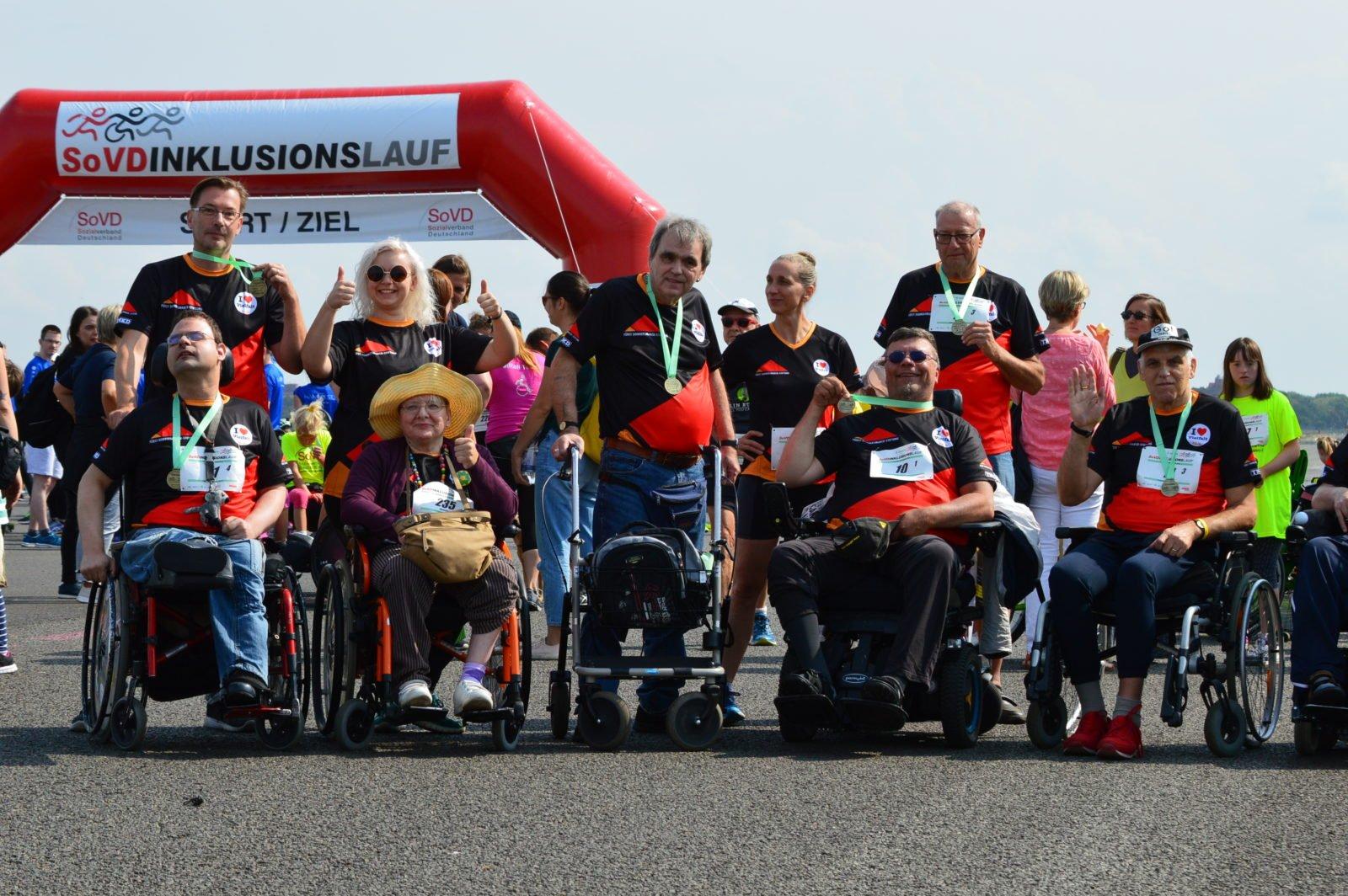 Eine Gruppe Menschen mit und ohne Rollstuhl posiert für ein Gruppenbild vor dem Start beim SoVD Inklusionslauf 2018. Alle tragen dieselben Trikots und Medaillien um den Hals.