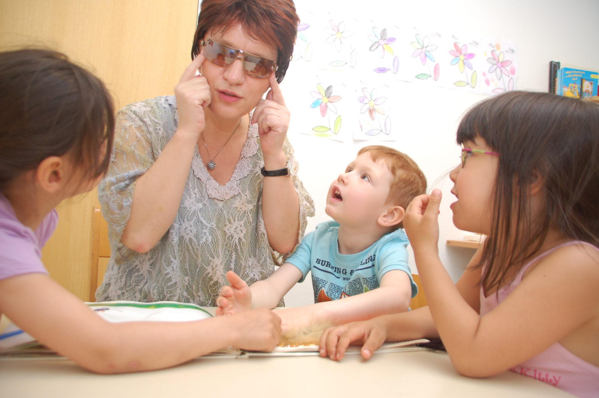 Silja Korn und mehrere Kita-Kinder sitzen zusammen. Die Kinder schauen ihre Erzieherin an.