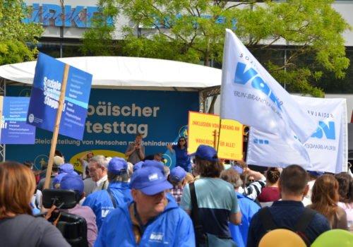Protesttag: Blick auf die Kundgebungsbühne des Europäischen Protesttags zur Gleichstellung von Menschen mit Behinderung. Im Vordergrund sind jede Menge Demonstranten, Transparente und Schilder im Bild zu sehen.