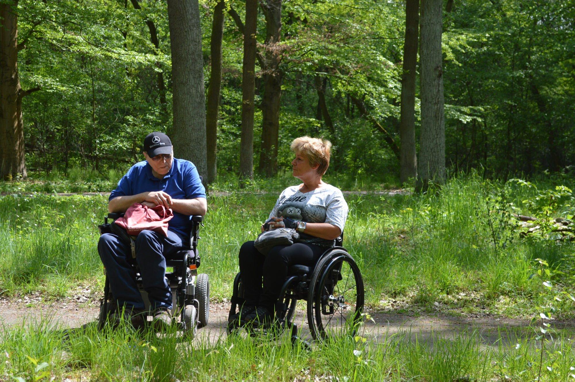 Ein Rollstuhlfahrer und eine Rollstuhlfahrerin stehen auf einem Weg im Wald. Um sie und den Weg herum stehen überall Bäume, Gras und Pflanzen.