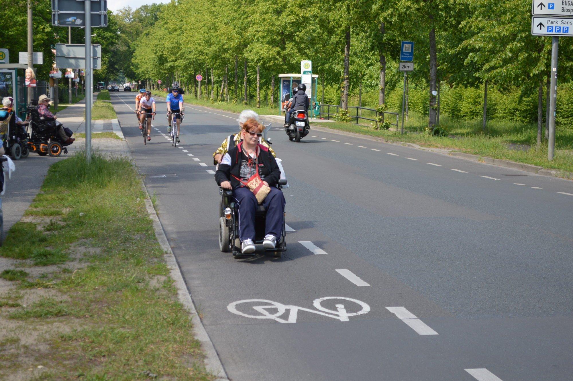 Eine Rollstuhlfahrerin fährt auf dem Fahrradweg. Im Hintergrund weitere Rolli- sowie Radfahrer.