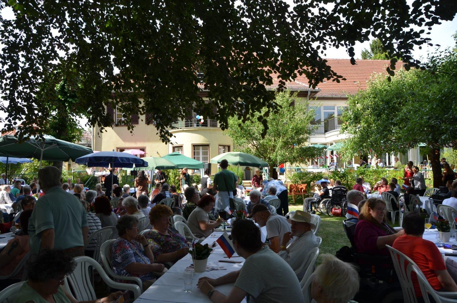 Viele Menschen sitzen an Gartentischen auf Gartenstühlen und in Rollstühlen im Garten. die Sonne scheint. Im Hintergrund sind Bäume und die Villa Donnersmarck zu sehen.