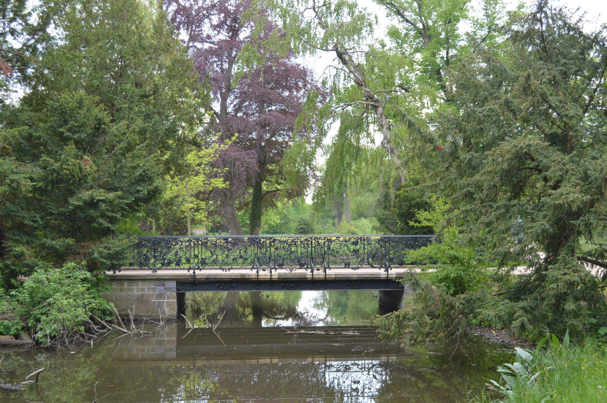 Eine Brücke über ein ruhiges Gewässer. Blühende Bäume und alles reflektiert auf der Wasseroberfläche.