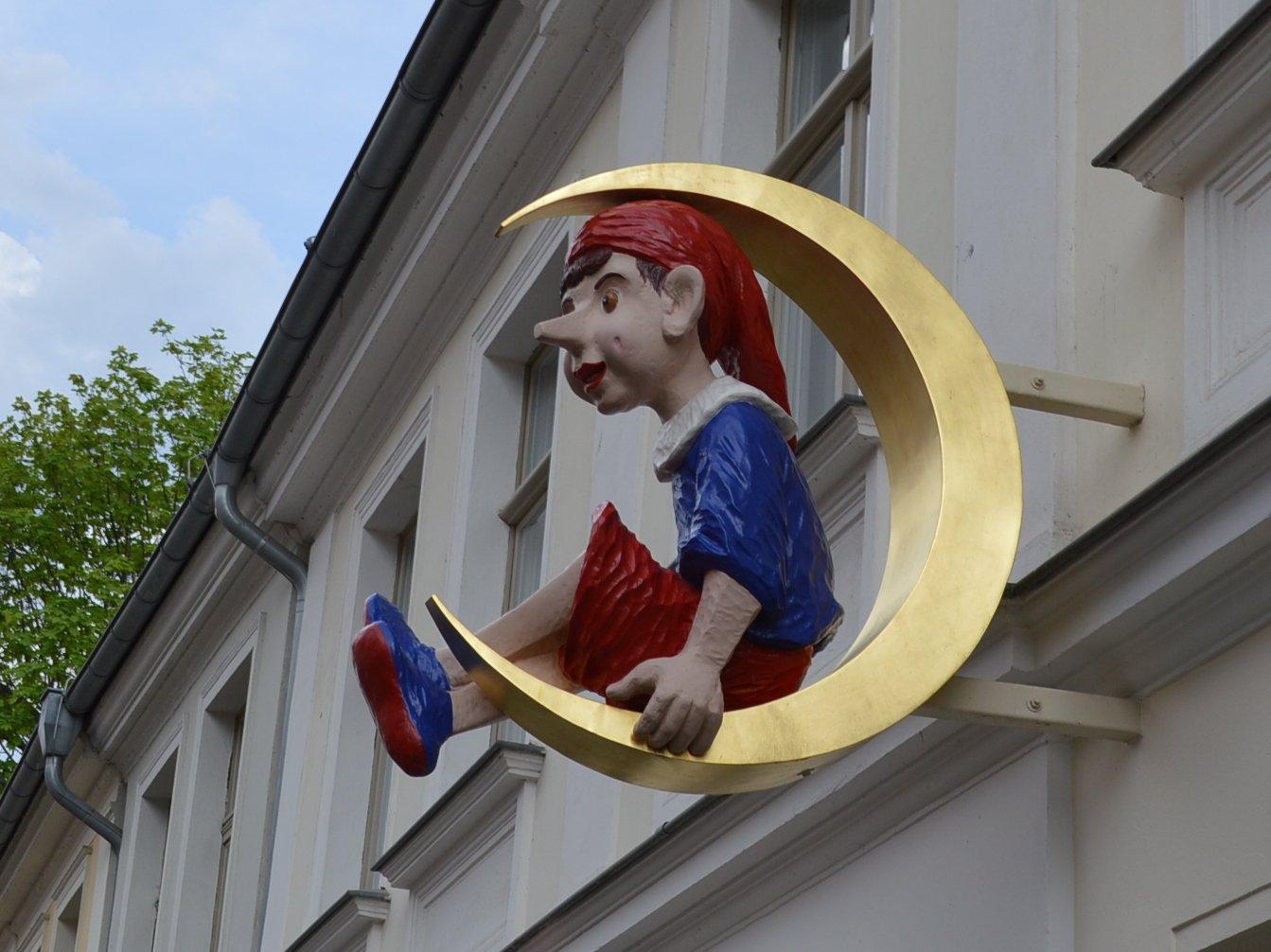 Schild an einer Hauswand: Ein Pinocchio mit roter Mütze sitzt in einem goldenen Halbmond.