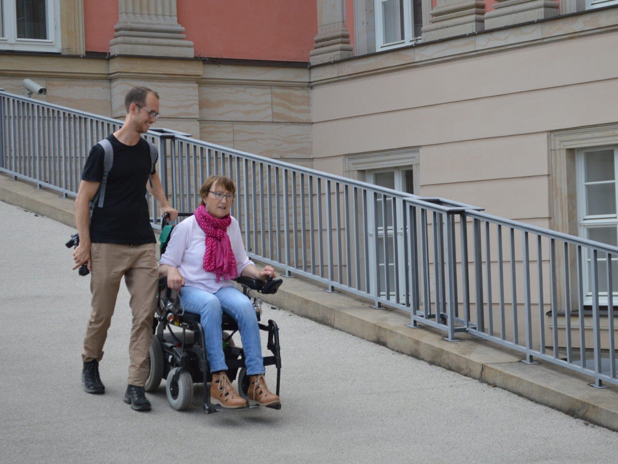 Ein Fußgänger und eine Rollstuhlfahrerin gehen eine Rampe hinunter.