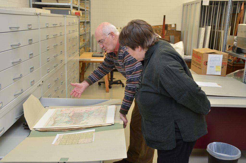 Gerd Heinemann öffnet eine Schublade des Archivschrankes und präsentiert Anke Köhler eine  ca. A2 große Mappe mit unterschiedlichen Landkarten.