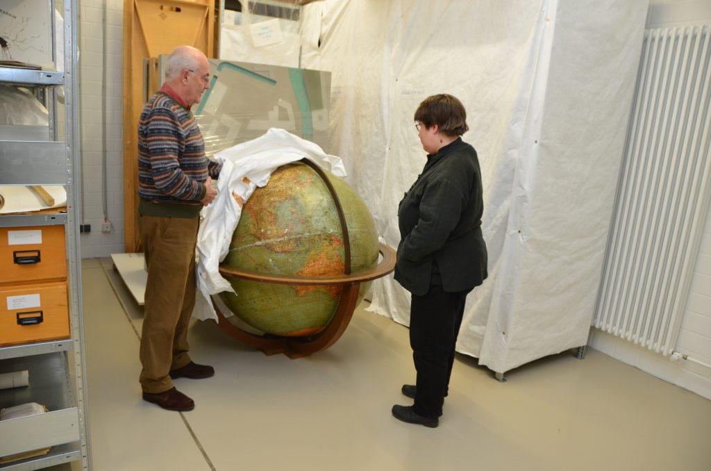 Gerd Heinemann zeigt Anke Köhler den großen Globus und entfernt dafür das Tuch, mit dem er abgedeckt ist.