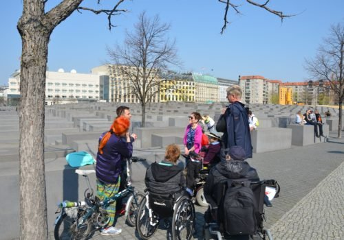 Eine Gruppe Menschen, darunter drei Rollstuhlfahrerinnen und -fahrer sowie eine Frau mit Fahrrad, steht gemeinsam vor dem Holocaust-Mahnmal in Berlin-Mitte. Der Himmel ist klar und die Sonne scheint.