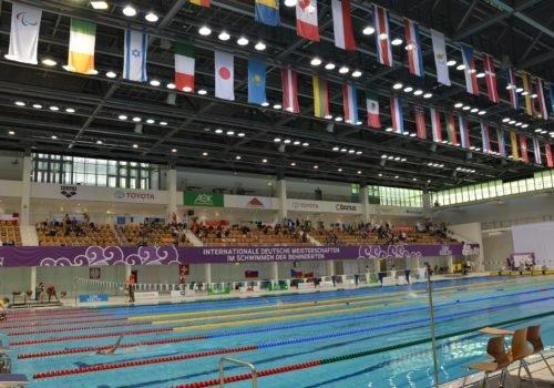 Blick in die Schwimmhalle: Vorne das Becken in dem gerade ein Wettkampf stattfindet, im Hintergrund die Ränge mit Zuschauern und darüber die Flaggen aller teilnehmenden Nationen.