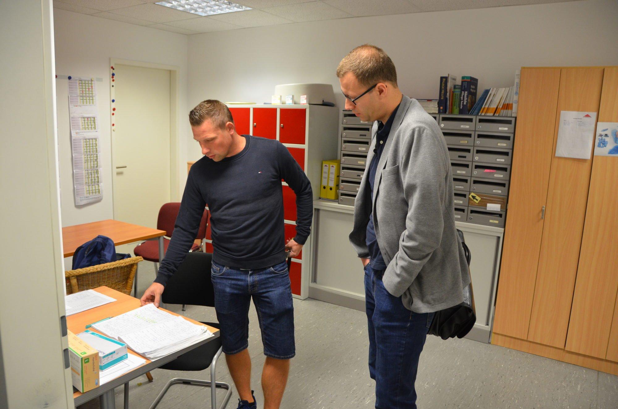 Pflegefachkraft Marco Noack im Büro des AD. Er zeigt Dr. Sebastian Weinert den Dienst- und Tourenplan.