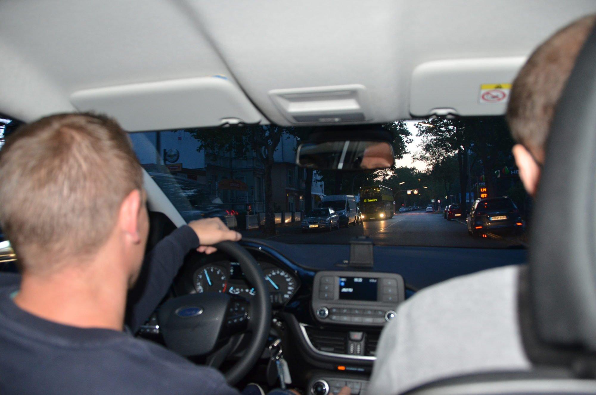 Vom Rücksitz des Autos über die Schultern von Marco Noack und Dr. Sebastian Weinert fotografiert. Es ist noch dunkel, auf der Straße fährt sonst nur ein Bus.