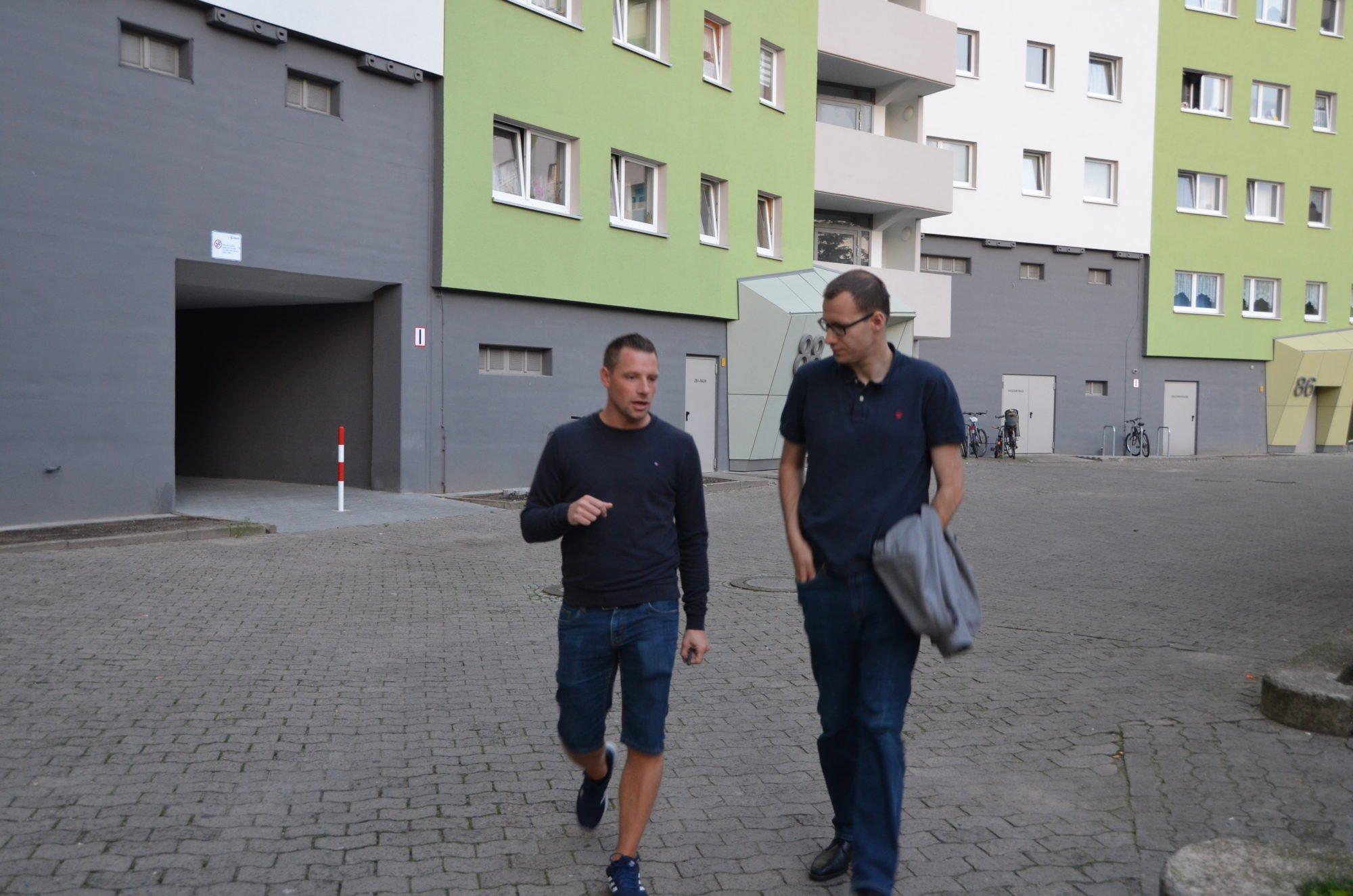 Die beiden laufen vor einem Plattenbau und unterhalten sich.