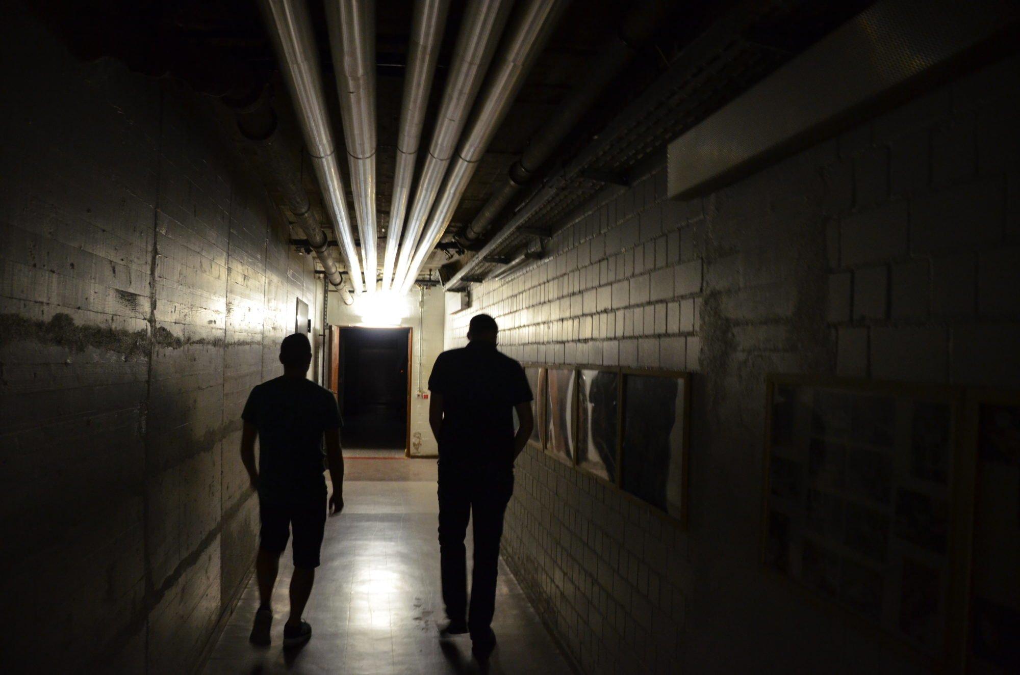 Marco Noack und Sebastian Weiner in einem schwach beleuchteten Kellergang.