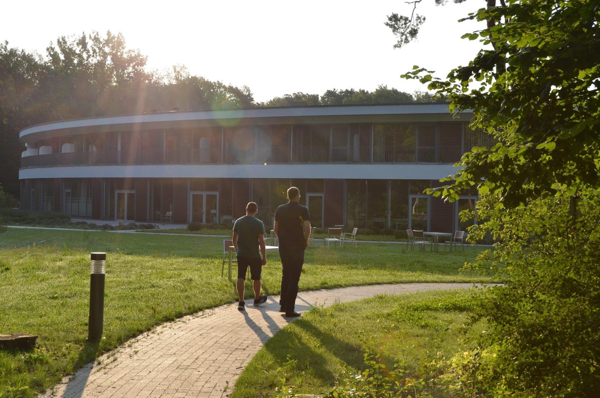 Marco Noack und Dr. Sebastian Weinert laufen auf das P.A.N. Zentrum zu. Darüber geht die Sonne auf.