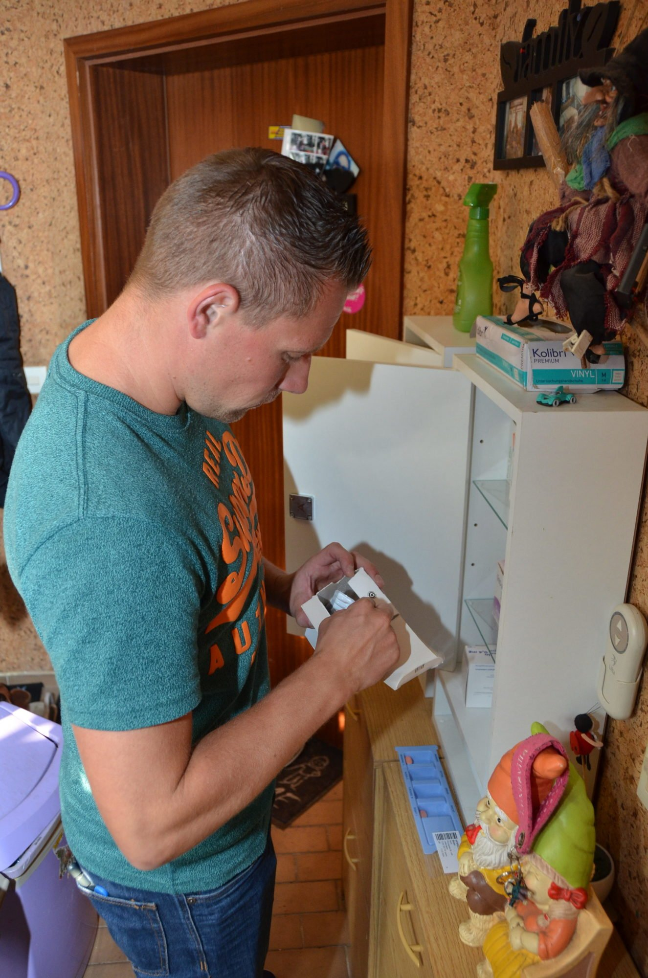 Marco steht in einem Hausflur an einem Medikamentenschrank und öffnet eine Schachtel.
