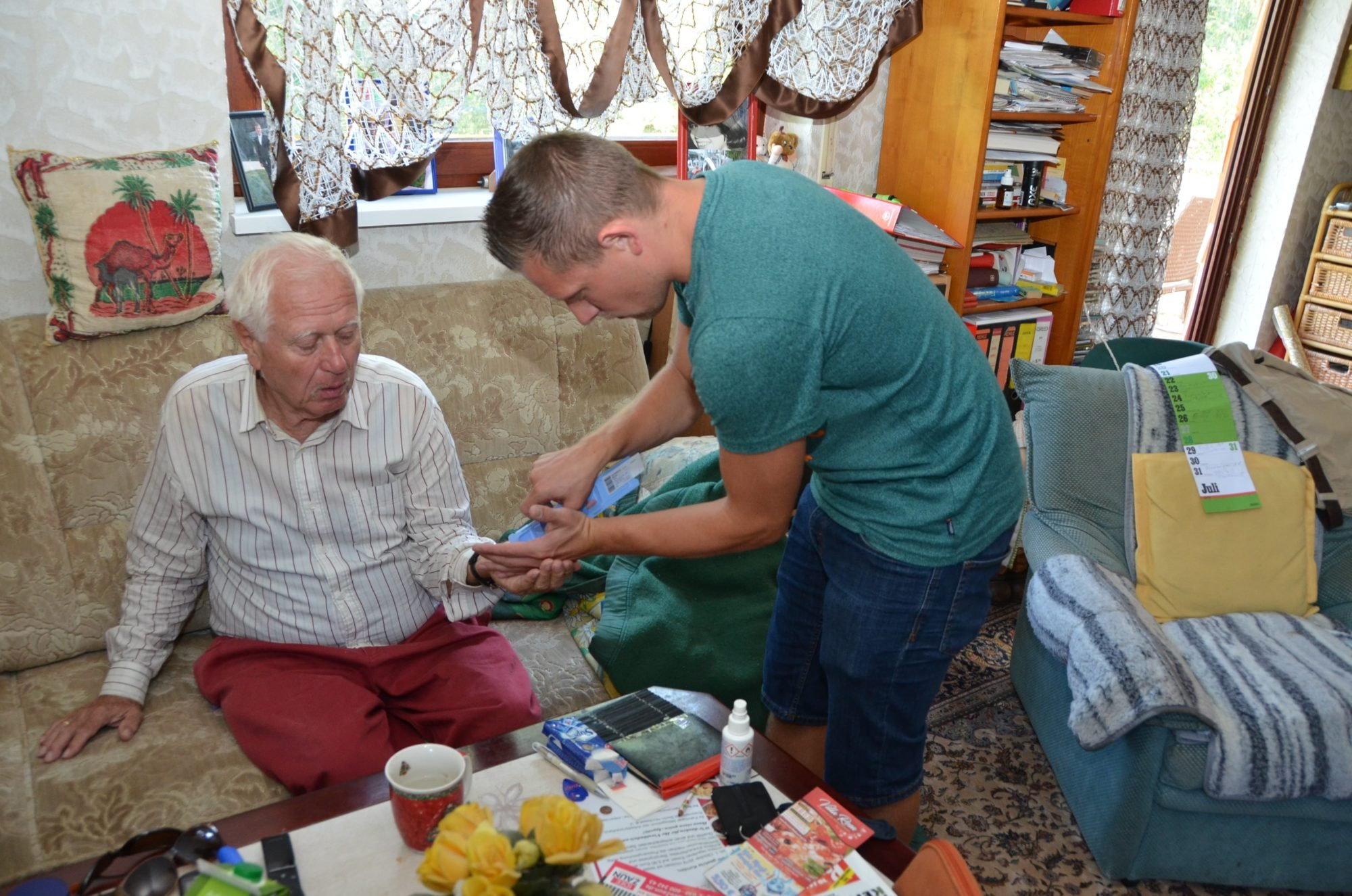 Marco, rechts im Bild ist leicht nach vorne gebeugt und gibt einem älteren Herren, der auf seinem Sofa sitzt, seine Medikamente in die Hand.