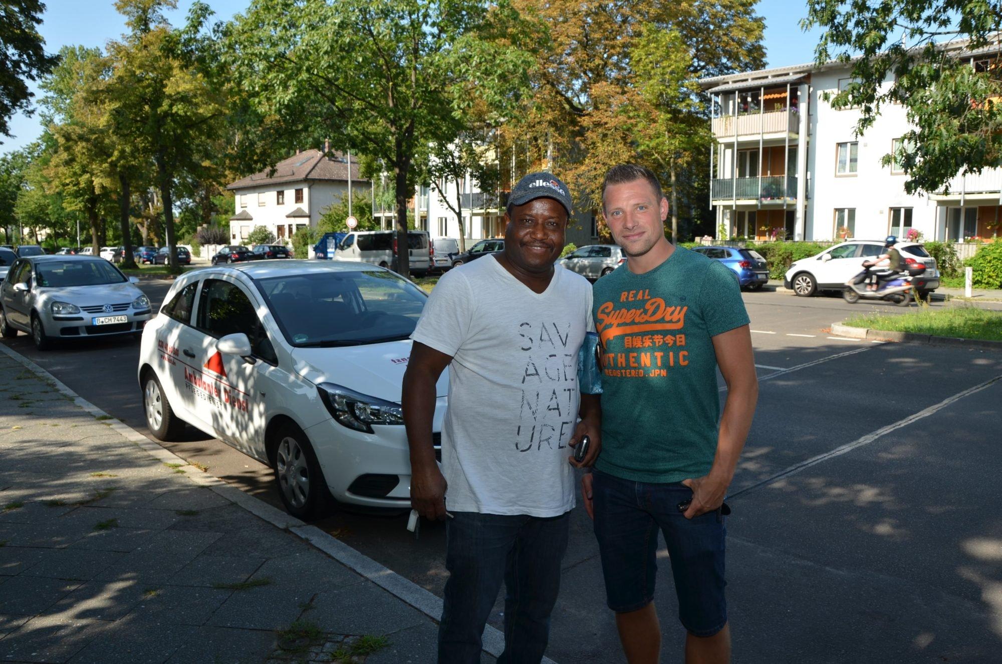 Marco und sein Kollege John posieren auf der Straße gemeinsam für ein Foto.