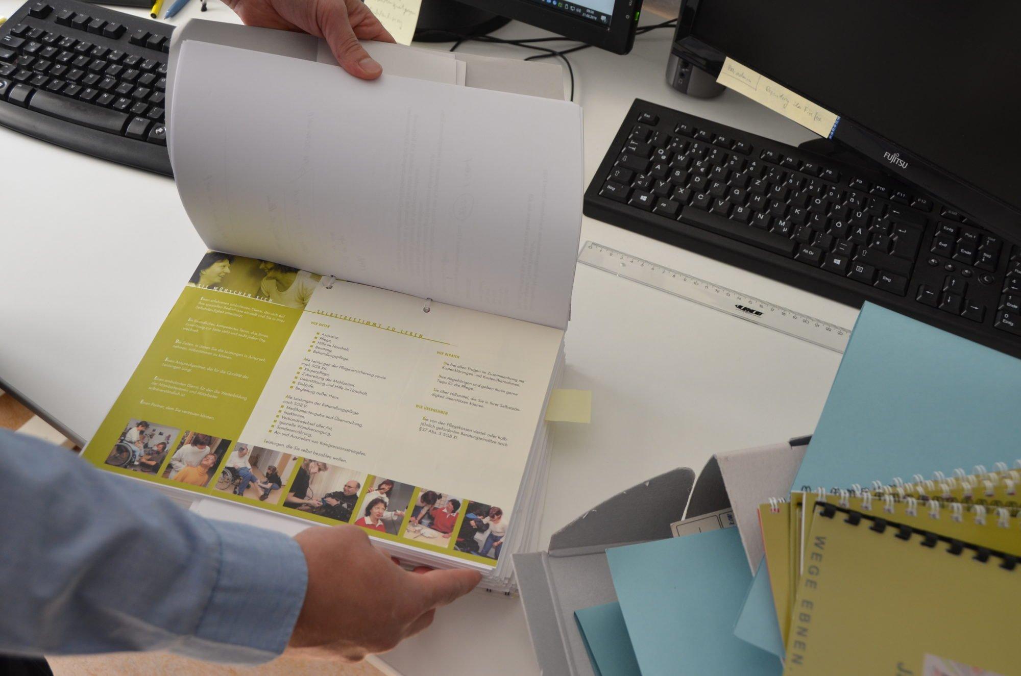 Hände halten einen Aktenordner offen, rechts daneben liegen weitere Akten. Im Hintergrund Tastaturen und Monitore auf dem Schreibtisch.