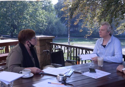 Sabine Haller und Martin Küster in der Interviewsituation im Freien an einem Holztisch.