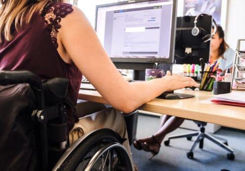 Eine junge Frau im Rollstuhl sitzt an ihrem Bildschirmarbeitsplatz. Im Hintergrund ist eine Kollegin zu sehen, die ebenfalls gerade an ihrem Bildschirm arbeitet.