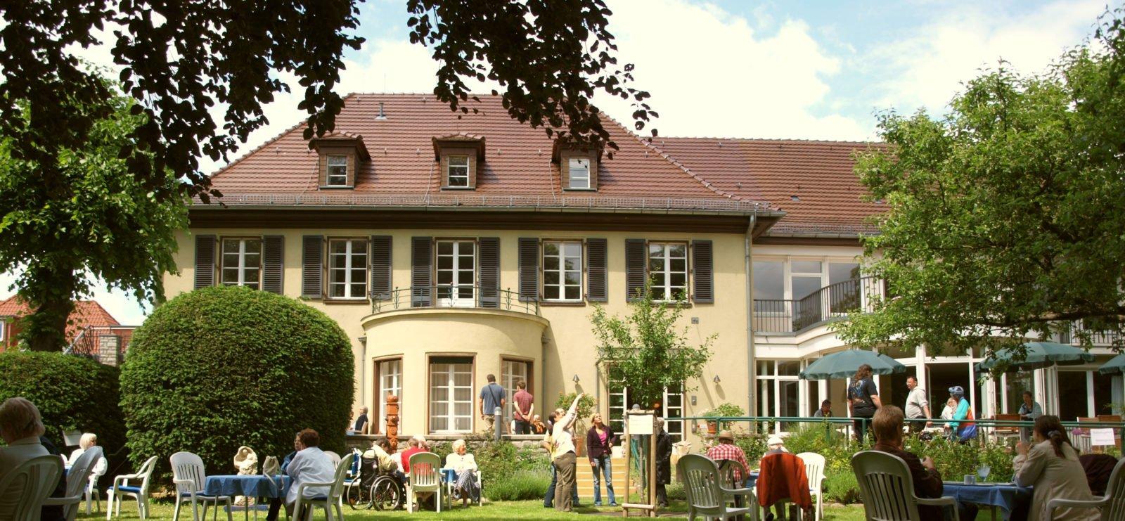 Ein Foto der Villa Donnersmarck. Im Vordergrund laufen Menschen durch den Garten oder sitzen an Tischen.
