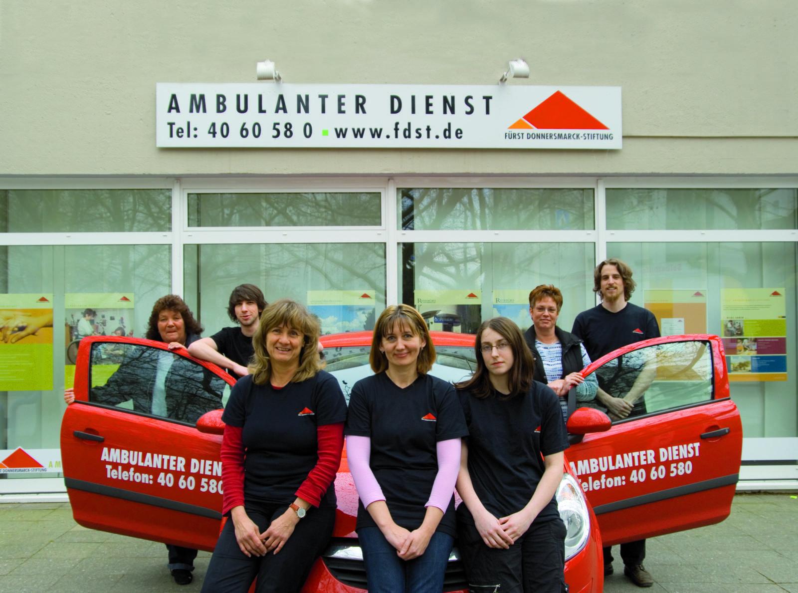 Gruppenfoto vor einem Auto und den Büros des Ambulanten Dienstes.