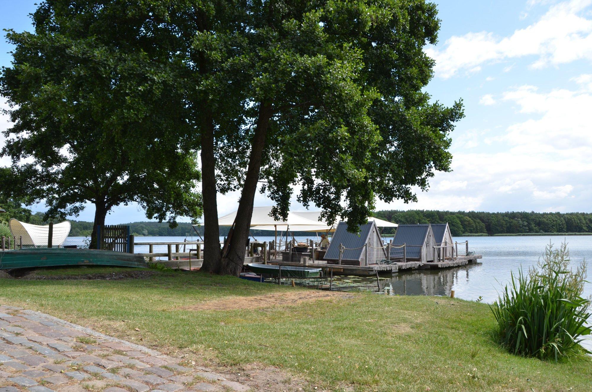 Im Vordergrund ein Kopsteinpflaster-Weg, dahinter ein großer Laubbaum. Hinter dem Baum sind die Floße aus Holz zu erkennen. Dahinter der See.
