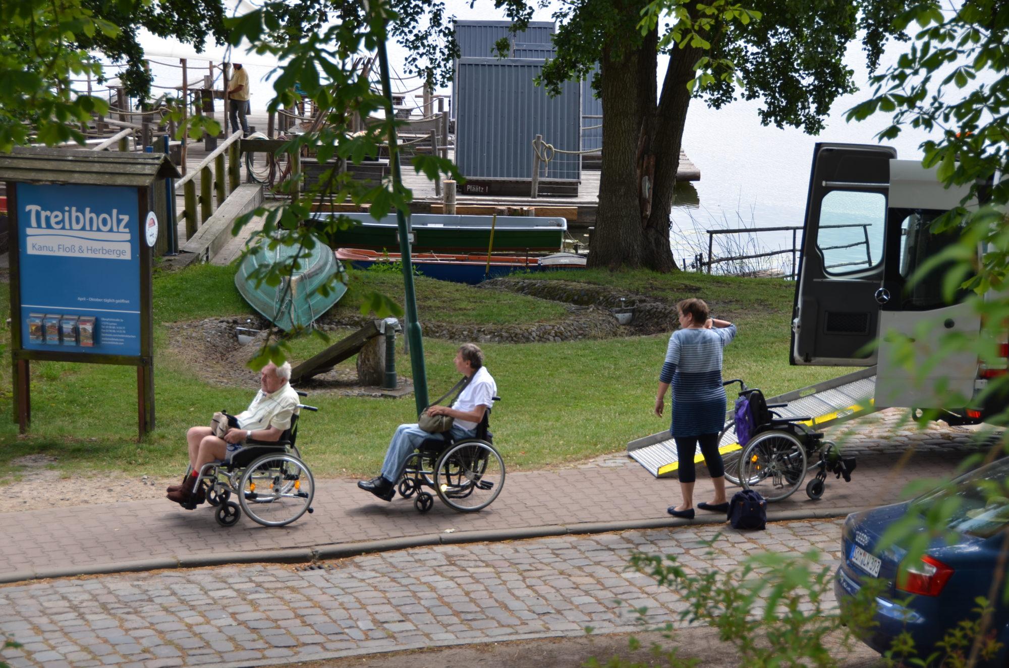 Rollstuhlfahrer steigen aus dem Bus und rollen auf den Gehweg.