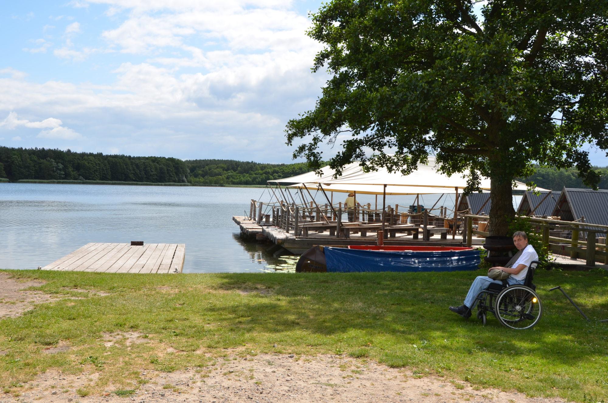 Die FLoße auf dem See. Im Vordergrund steht ein Rollstuhlfahrer.