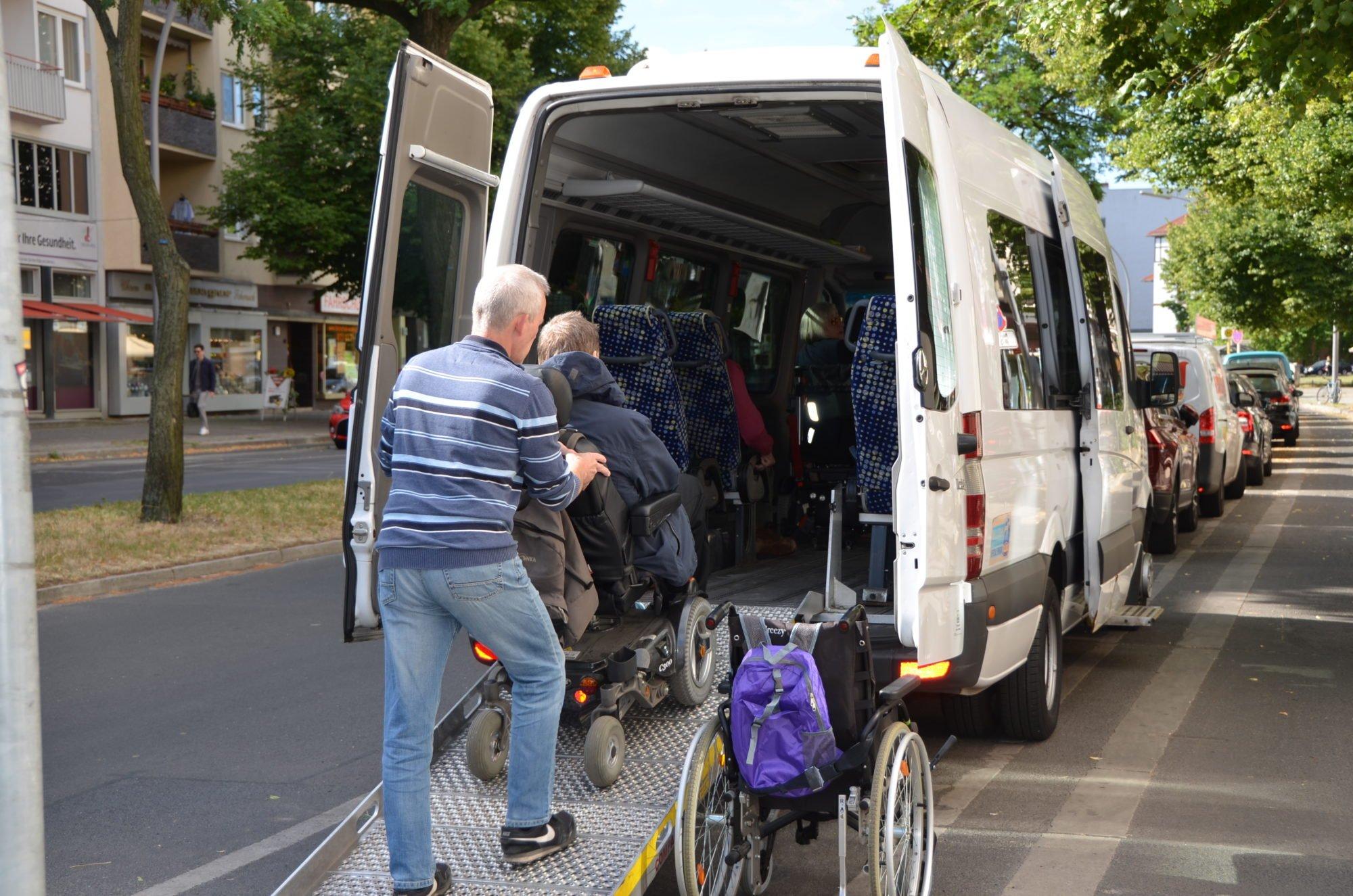 Von hinten fotografiert: ein Mann hilft einem Mann im E-Rollstuhl die Rampe in einen Sprinter-Bus hinein,