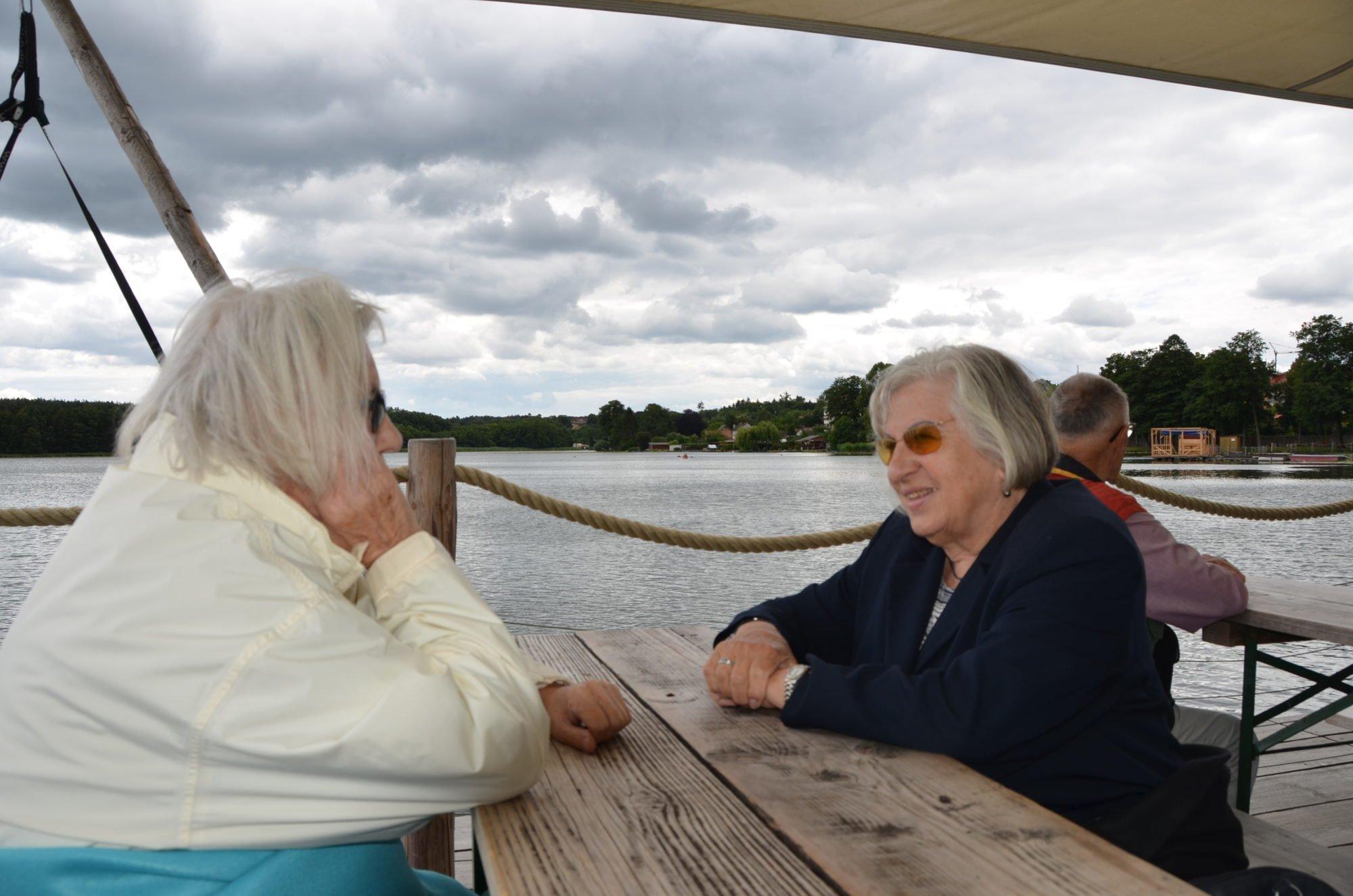 Zwei ältere Damen sitzen an einem Holztisch auf dem Floß und unterhalten sich.