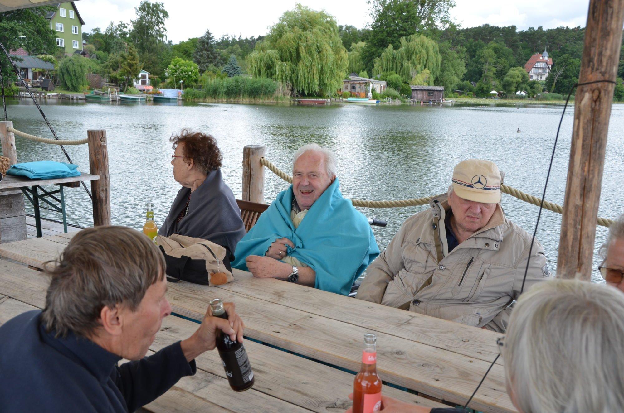 Die Reisegruppe an einem Holztisch auf dem Floß.