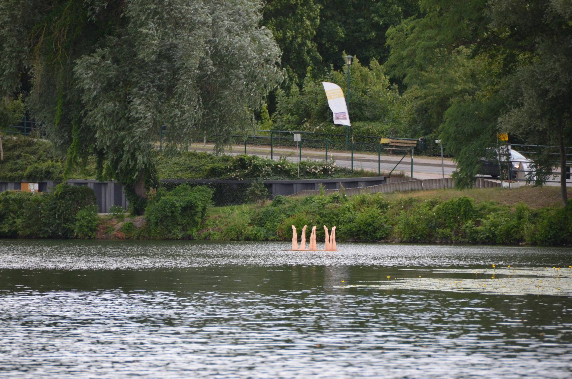 Das Kunstwerk auf dem See: vier Paar Beine ragen aus dem Wasser nach oben.