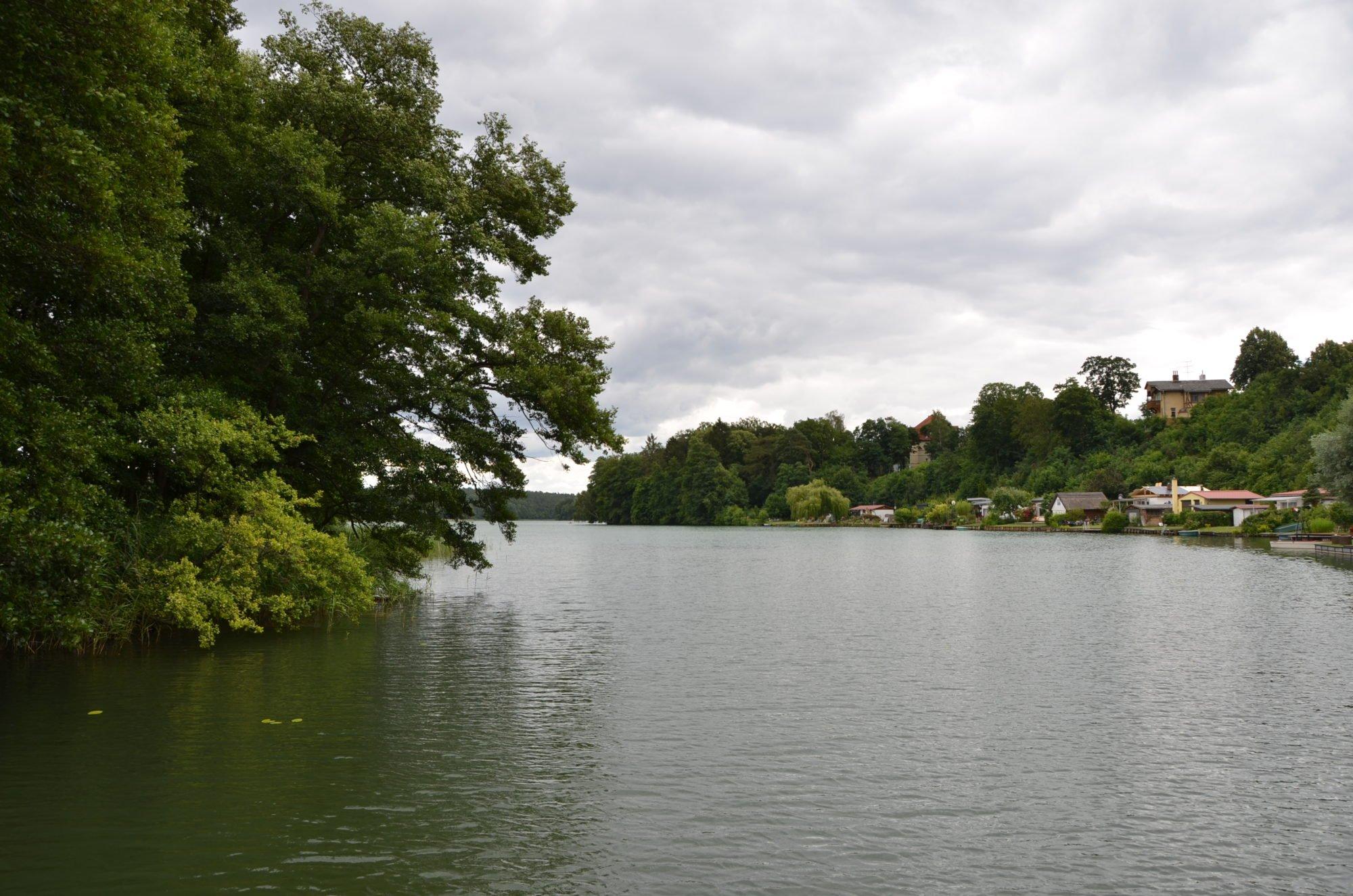 Um die Ecke, von einem See auf den anderen. Im Hintergrund viele Bäume und dazwischen Häuser.
