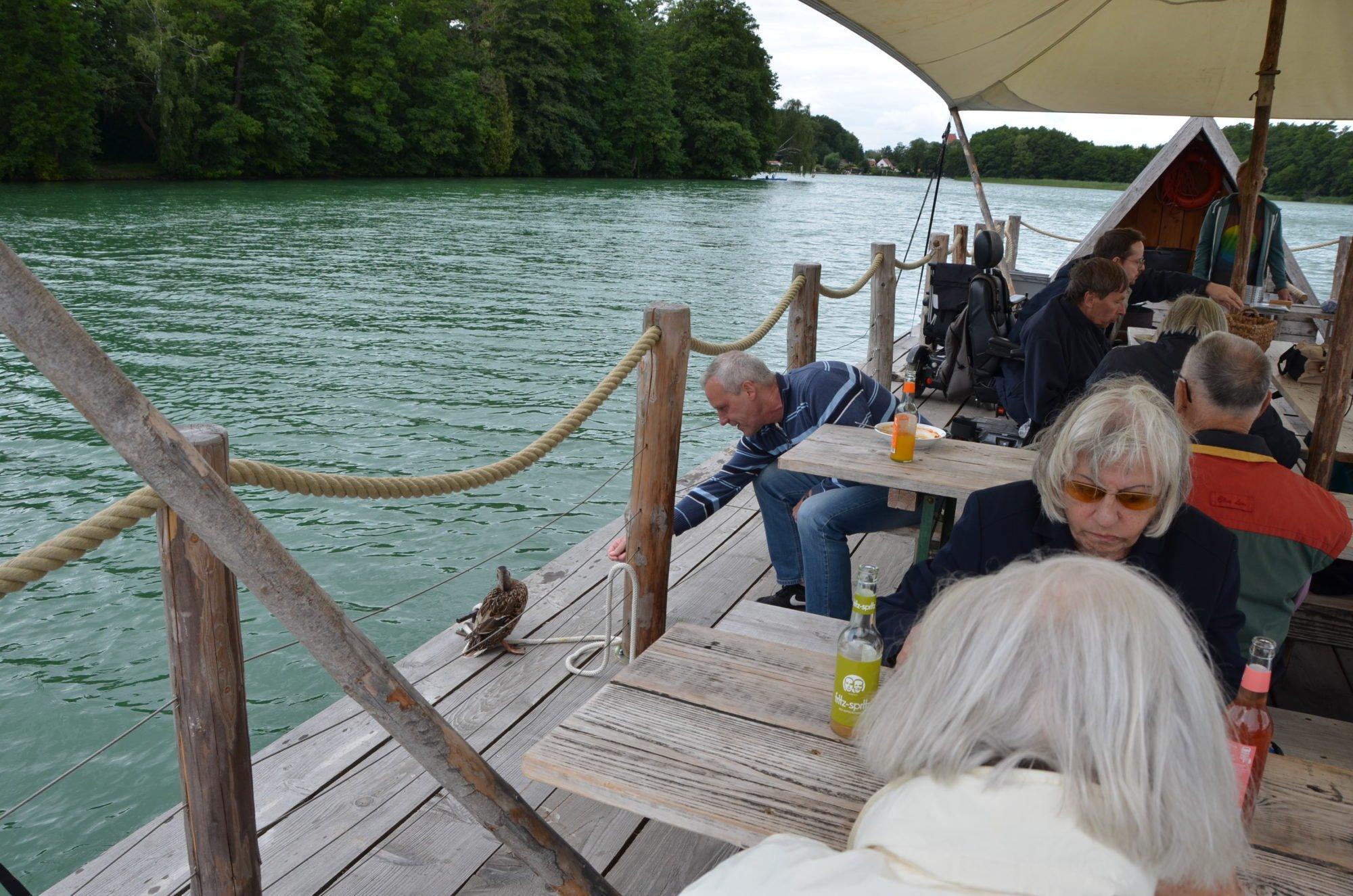 Busfahrer John füttert eine Ente, die auf das Floß gekommen ist.