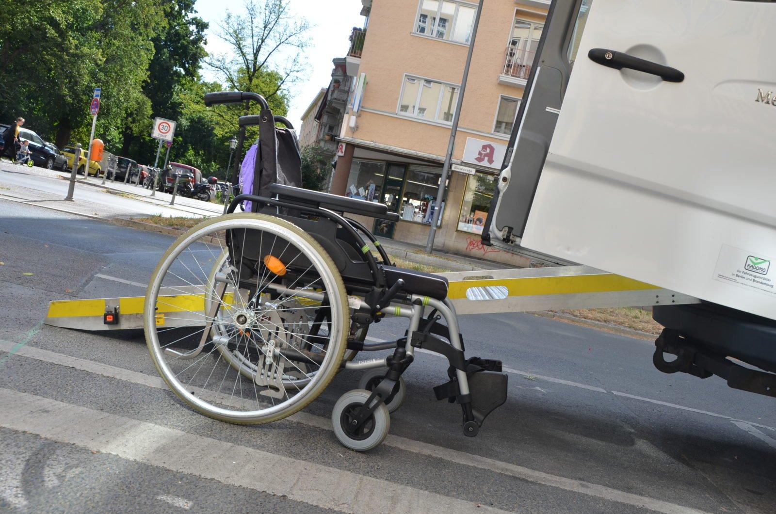Ein leerer Rollstuhl steht vor einem Sprinter-Bus mit Rampe.