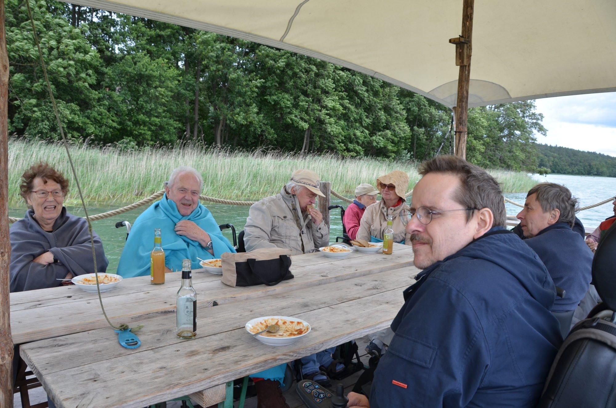 Die Laune in der Gruppe ist bestens. Alle sitzen mit Jacken und Decken auf dem Floß.