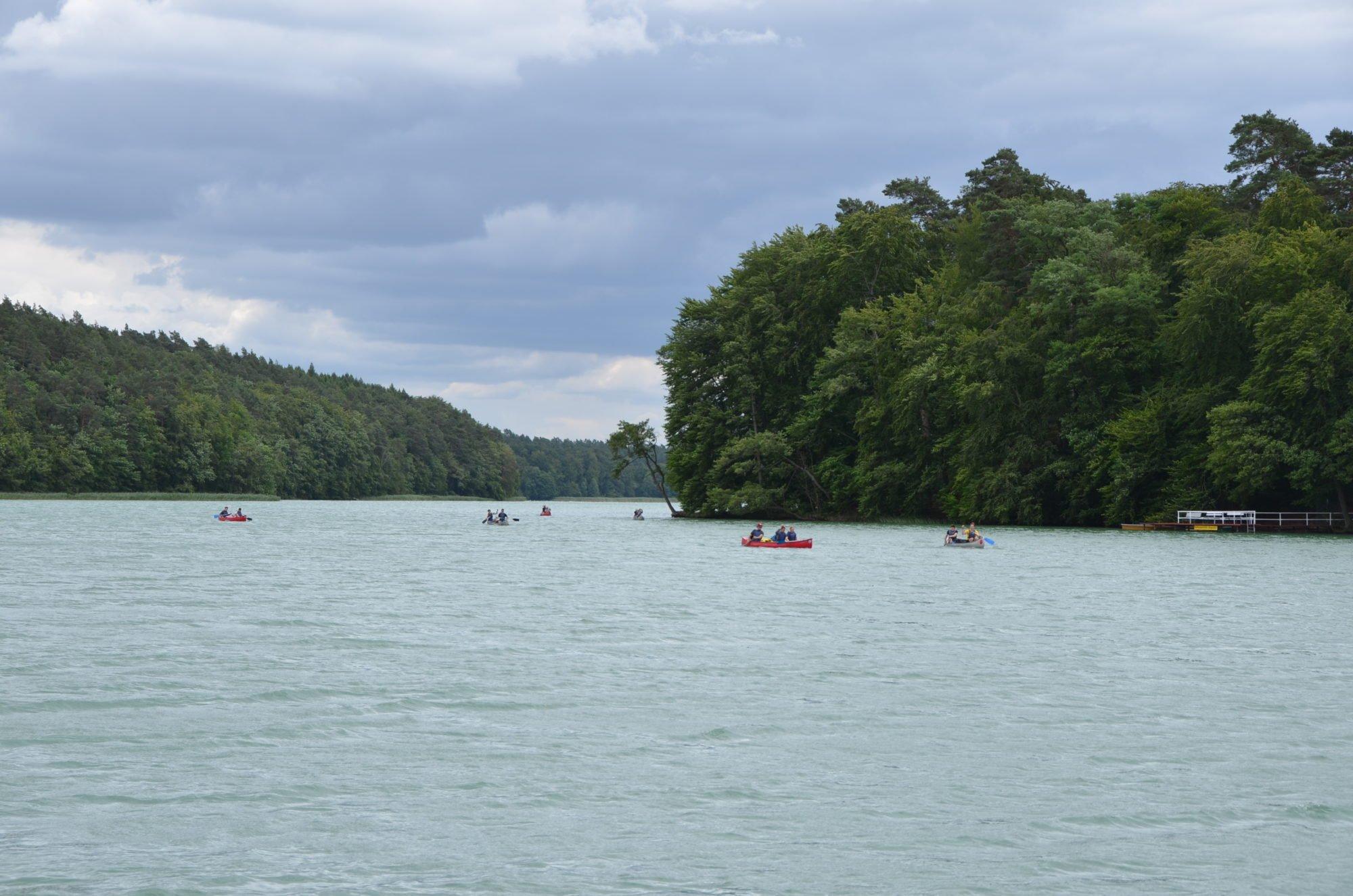 Kanufahrer kommen dem Floß auf dem See entgegen.