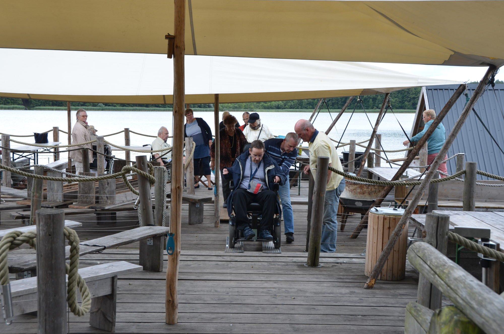 Ein E-Rollstuhl-Fahrer beim Ausstieg über die Rampen auf dem Floß.