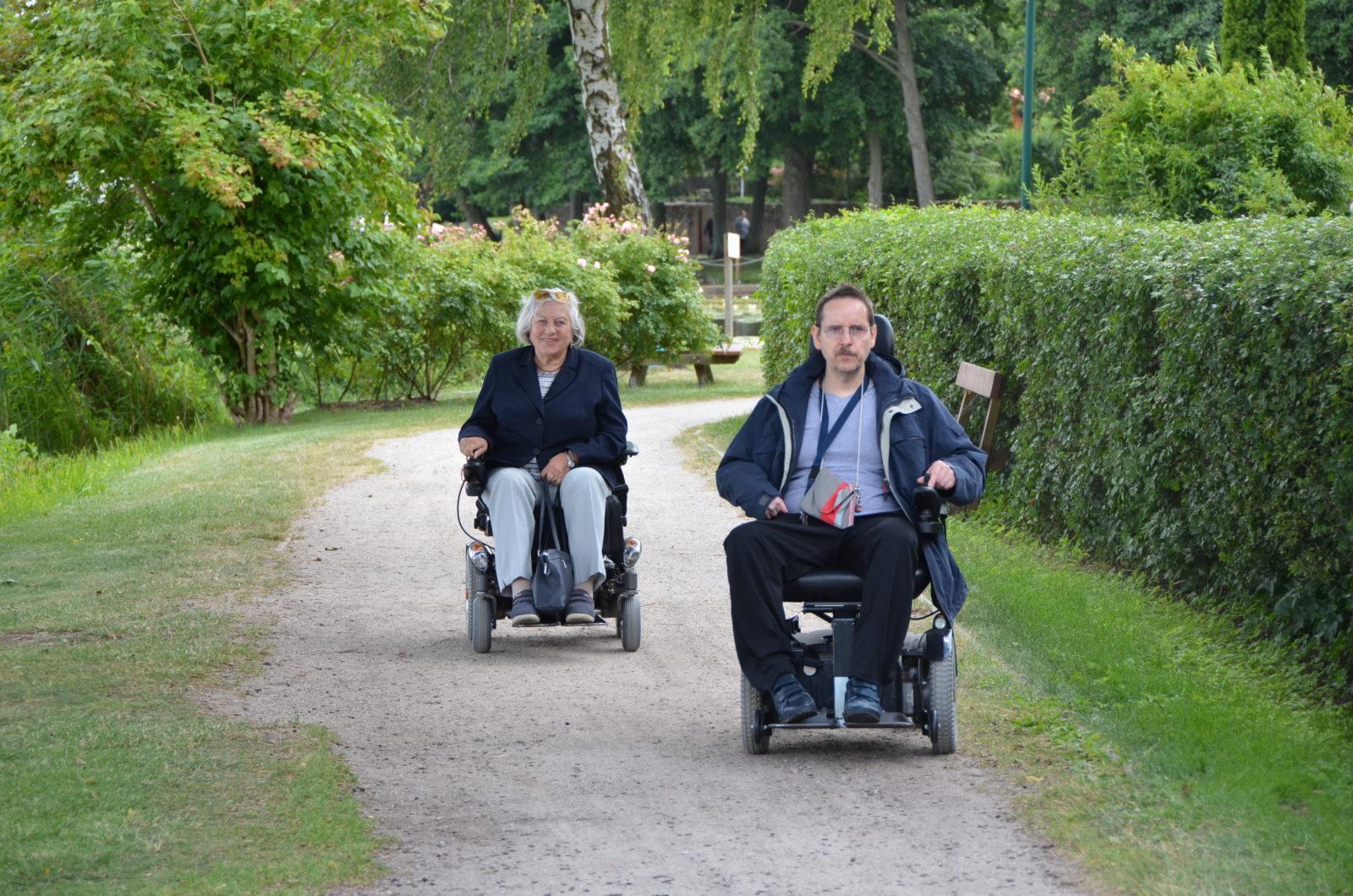 Ein E-Rolli-Fahrer und eine E-Rolli-Fahrerin fahren auf einem kleinen Fahrradweg auf die Kamera zu und lächeln.
